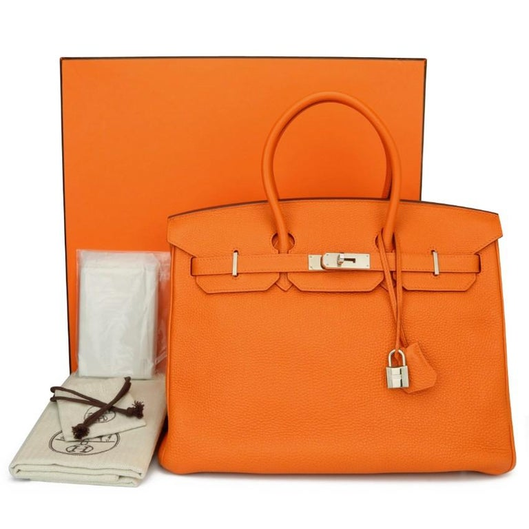 Hermes Birkin Bag 35cm Orange Togo Leather with Palladium Hardware Stamp N_Year 2010  This bag is still in excellent-mint condition. The bag still holds to the shape well. The hardware still very shiny and covered by the original protective