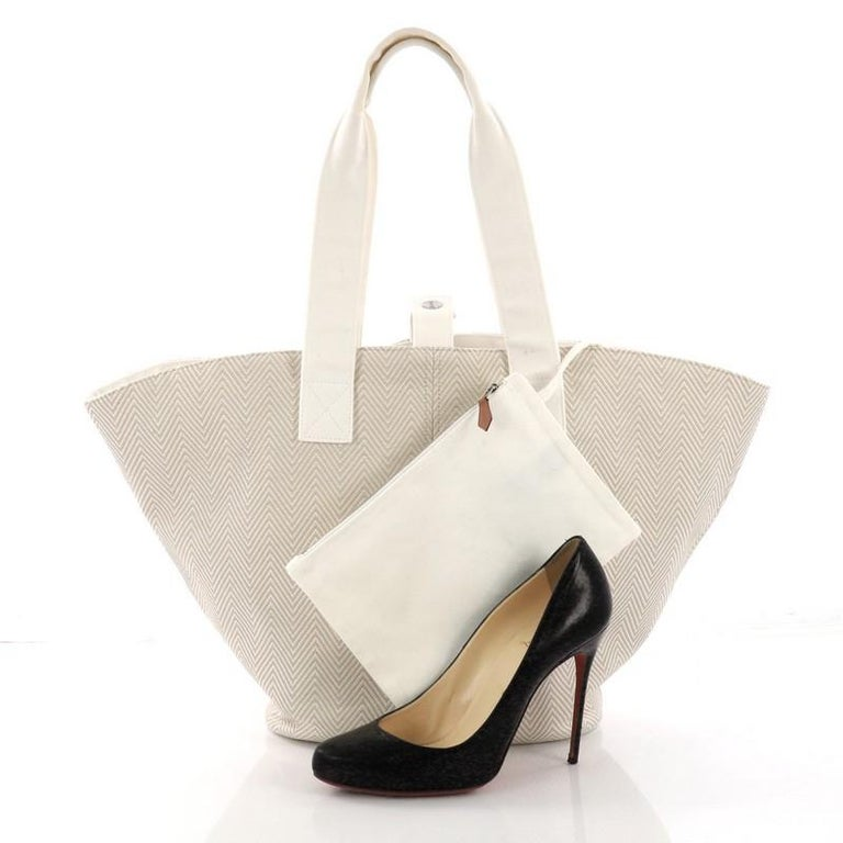 This Hermes Panier De Plage Handbag Canvas PM, crafted in beige ecru toile canvas, features dual flat handles and palladium-tone hardware. Its wide open top showcases a white canvas interior. **Note: Shoe photographed is used as a sizing reference,