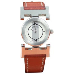 Hermès Paprika watch with a brown leather strap.