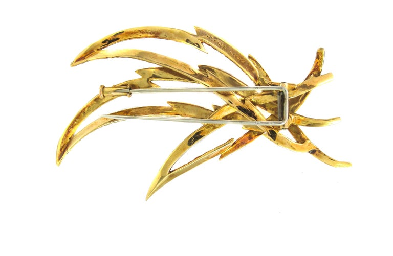 Beautifully designed and handcrafted designer brooch signed Hermes Paris. The abstract and three dimensional open gold work, typical of the '70s depicts three intertwining flames rising. A chic and wearable piece, and a collectible at the same
