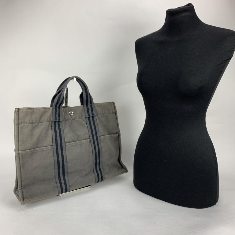 'HERMES FOURRE TOUT - MM' - Tote handbag. Made in France. Grey color with black stripes. Material: 100% cotton. It has snaps on both ends for expansion. Durable canvas handles, perfect for casual and everyday use. 3 open pockets on the front and 3