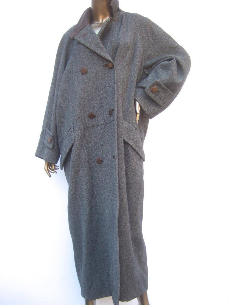 Hermes Paris Gray heavy gauge wool leather trim unisex winter coat c 1970s The stylish vintage Hermes heavy wool coat is designed with a brown leather collar Paired with brown leather square buttons that run down the front   The coat is lined in