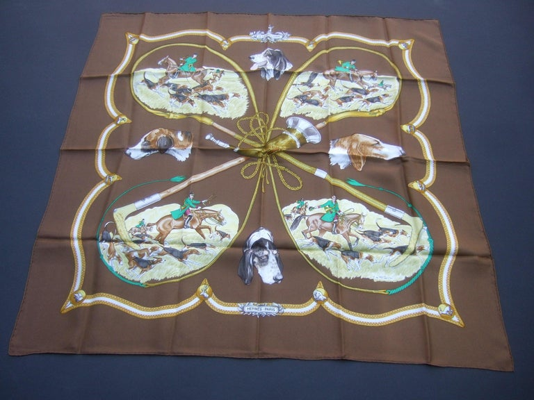 Hermes Paris silk equestrian hunt scene hand rolled scarf c 1990s  35 x 35 The elegant designer scarf is illustrated with a group of huntsman surrounded with their pack of hunting dogs  The equestrian riders and hunt dogs are illuminated against  a