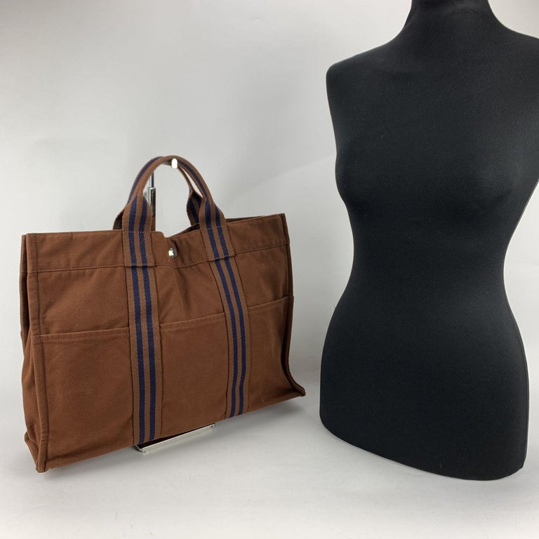 Hermes Paris Vintage brown cotton canvas tote, Fourre Tout MM. Made in France. Blue stripes. 100% Cotton. 3 front pockets on the front and 3 pockets on the back. It has snaps (buttons) on both ends for expansion. Durable canvas handles, perfect for