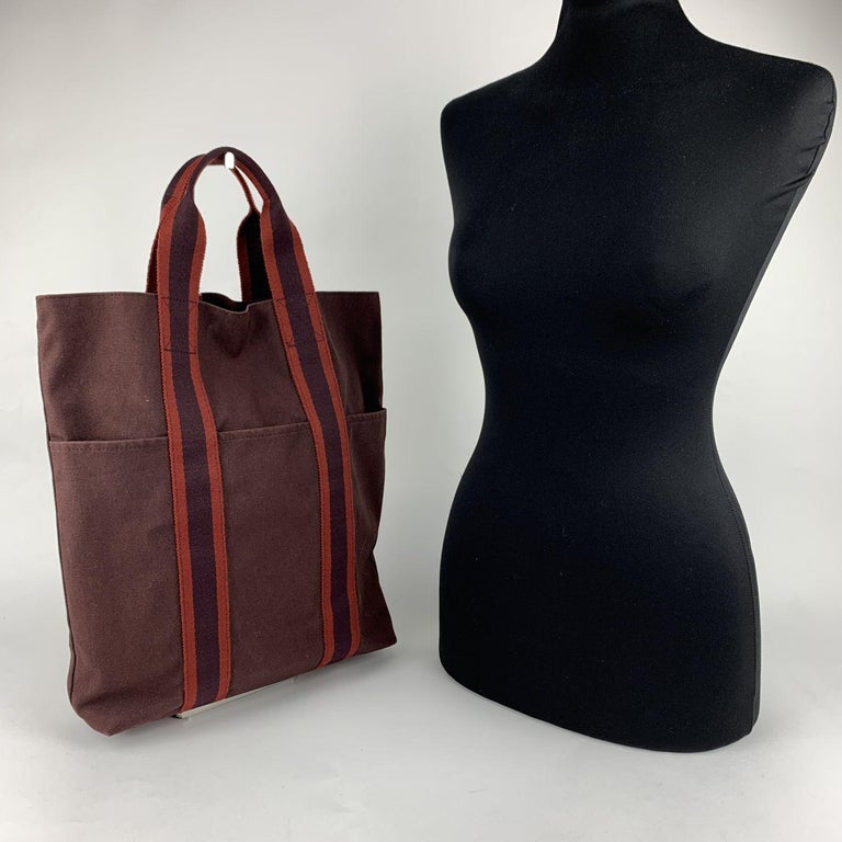 Model: 'HERMES Vertical FOURRE TOUT ' Shopping Bag. Made in France. Brown/burgundy color with red stripes. Material: 100% cotton. Durable canvas handles, perfect for casual and everyday use. Open top. 3 open pockets on the front Canvas internal