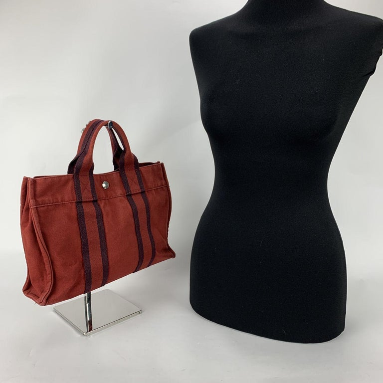 Model: 'HERMES FOURRE TOUT - PM' Tote handbag. Made in France. Red color with blue stripes. Material: 100% cotton. It has snaps on both ends for expansion. Durable canvas handles, perfect for casual and everyday use. Open top with middle snap