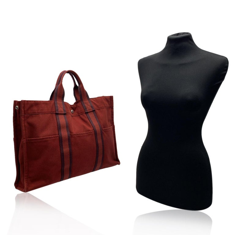 'HERMES FOURRE TOUT - MM' - Tote handbag. Made in France. Brown/burgundy color with red stripes. Material: 100% cotton. It has snaps on both ends for expansion. Durable canvas handles, perfect for casual and everyday use. Open top with middle snap