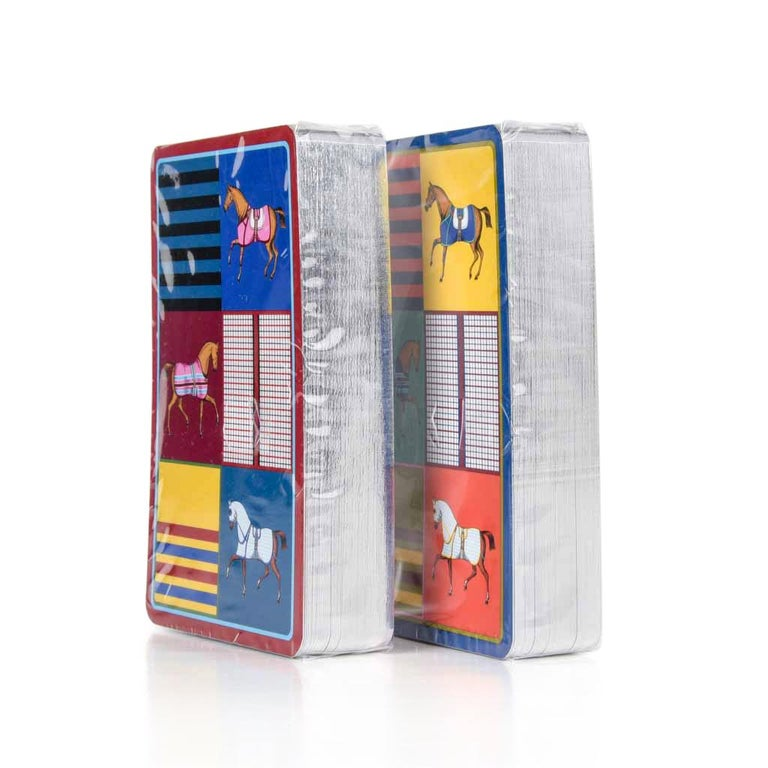 Guaranteed authentic Hermes Couvertures Nouvelles Bridge playing cards.  Sets are multicolored depicting horses with blankets and stripes.   The cards are new and sealed. Set includes two 54 cards decks.  Comes with signature Hermes box and ribbon.