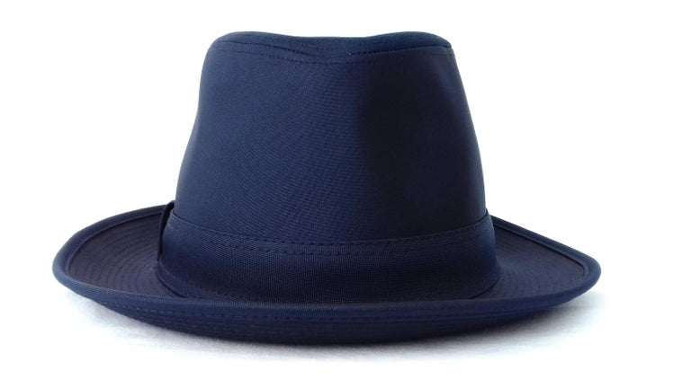 Beautiful Authentic Hermès Hat  Made in France  Made of Polyester and Polyamide  Lining in Acetate  Colorway: Navy Blue  Decorated with a navy blue fabric band, with an H embroidered on a bow  Size: tag says 56, but inner circumference makes 55 cm