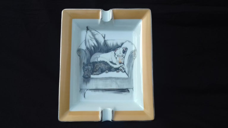 Rare Authentic Hermès Ashtray  Pattern: 2 dogs napping on an armchair  Made in France  Made of Printed Porcelain and Silver-Tone edges  Colorways: White Background, Beige Border, Black Grey and White drawings