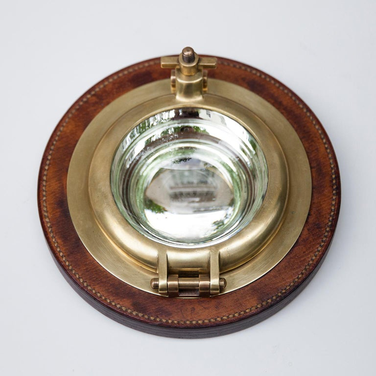 Super rare Hermes Porthole bowl, vide poche, made in solid brass, hand stitched leather and a mirrored inlay all based on a plywood base. Perfect for cufflinks or ashtray. Signed Hermes Paris on the bottom.