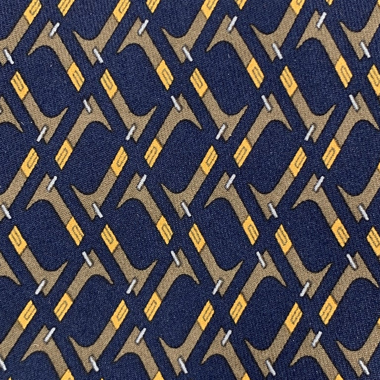 HERMES necktie comes in navy silk twill with an all over brown abstract pattern. Made in France.  Excellent Pre-Owned Condition. Marked: 7147 FA  Width: 3.5 in.