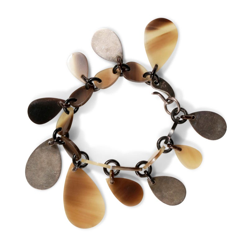 This authentic Hermès Raji Horn Bracelet is in excellent condition.  Neutral colored lacquered buffalo horn teardrop shaped charms dangle all the way around this natural bracelet.  Sterling silver hooked clasp. Box or pouch included.