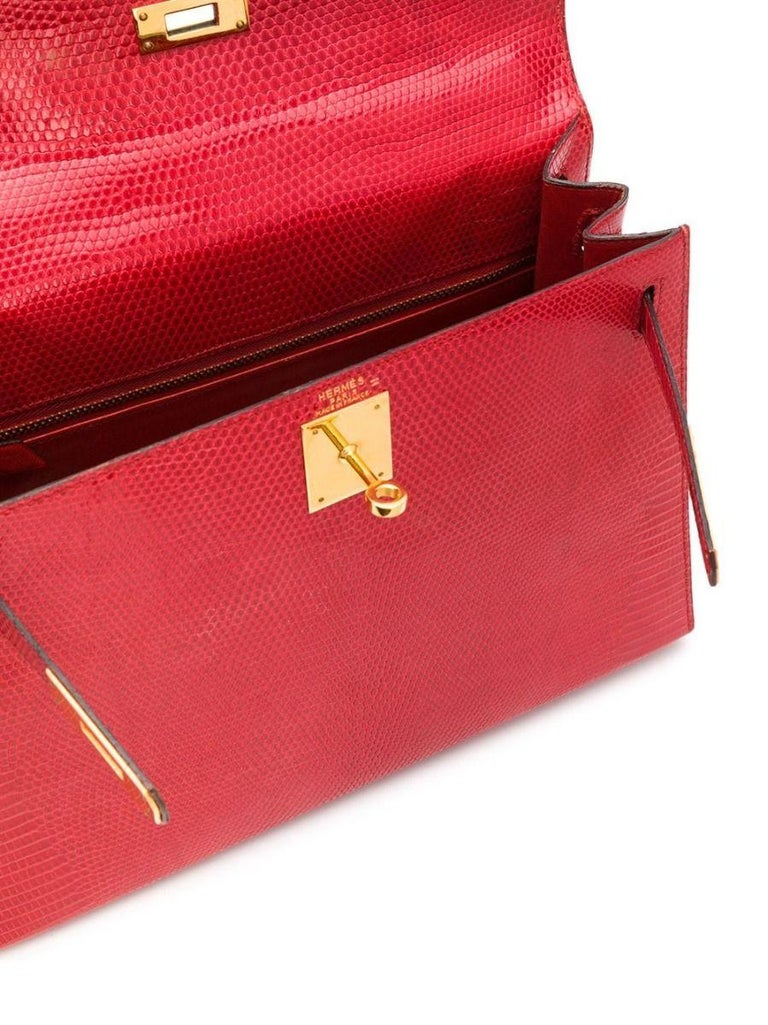 Crafted in France from lizard leather, a rare exotic Hermès skin known for its small scales and noticeably glossy finish. this structured, vintage bag features rigid corners and matching stitching with concealed piping. Featuring a vivid red