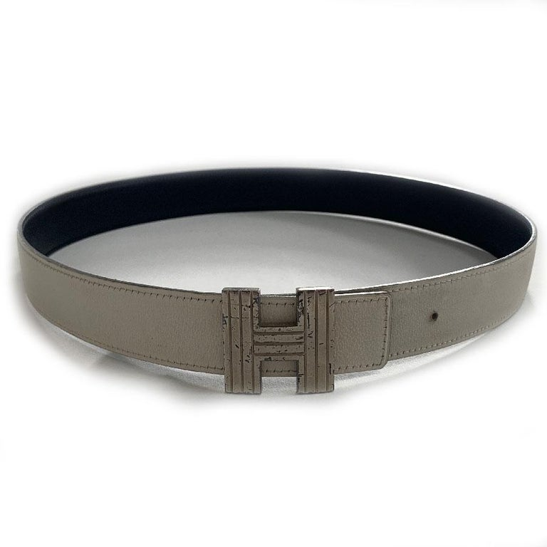 Iconic HERMES reversible belt in off-white and black color. Striated H buckle in silver metal. This belt, very popular because of its buckle, will fill your wardrobe. Its small width will allow you to wear it even on trousers with small