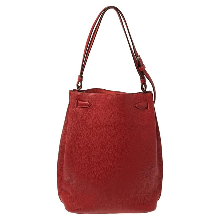 The elegant and timeless elements of the iconic Kelly is coupled with a more casual silhouette in this coveted So Kelly bag. It is crafted from red Togo leather in a slight bucket shape with the signature Kelly lock, in silver-tone on the front and
