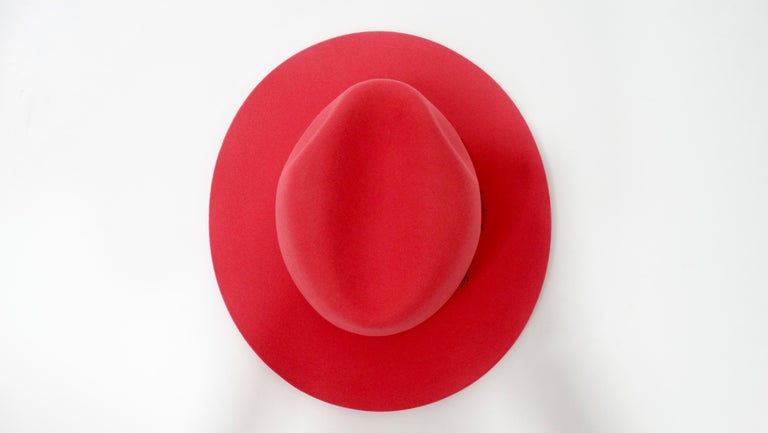 For the ultimate Hermés lover! Circa 21st century, this beautifully structured fedora is crafted from ultra soft rabbit felt with a rouge red finish. Around the base of the crown is a grosgrian rouge red ribbon. Interior is lined with an Hermés