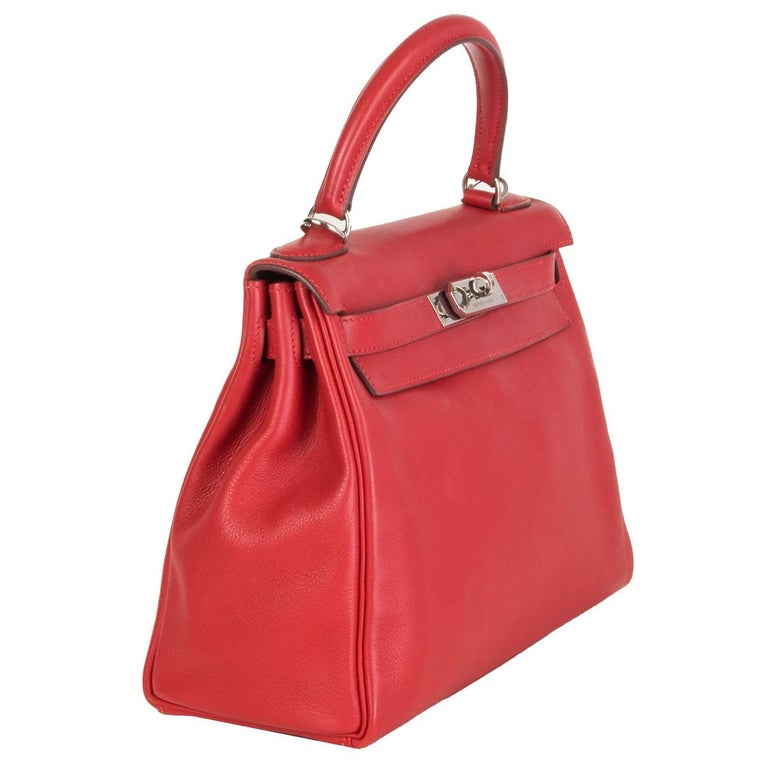 100% authentic Hermes 'Kelly 28 Retourne' bag in Rouge Tomate red Swift leather with palladium hardware. Lined in Chevre (goat skin) with an open pocket against the front and a zipper pocket against the back. Has been carried and is in excellent