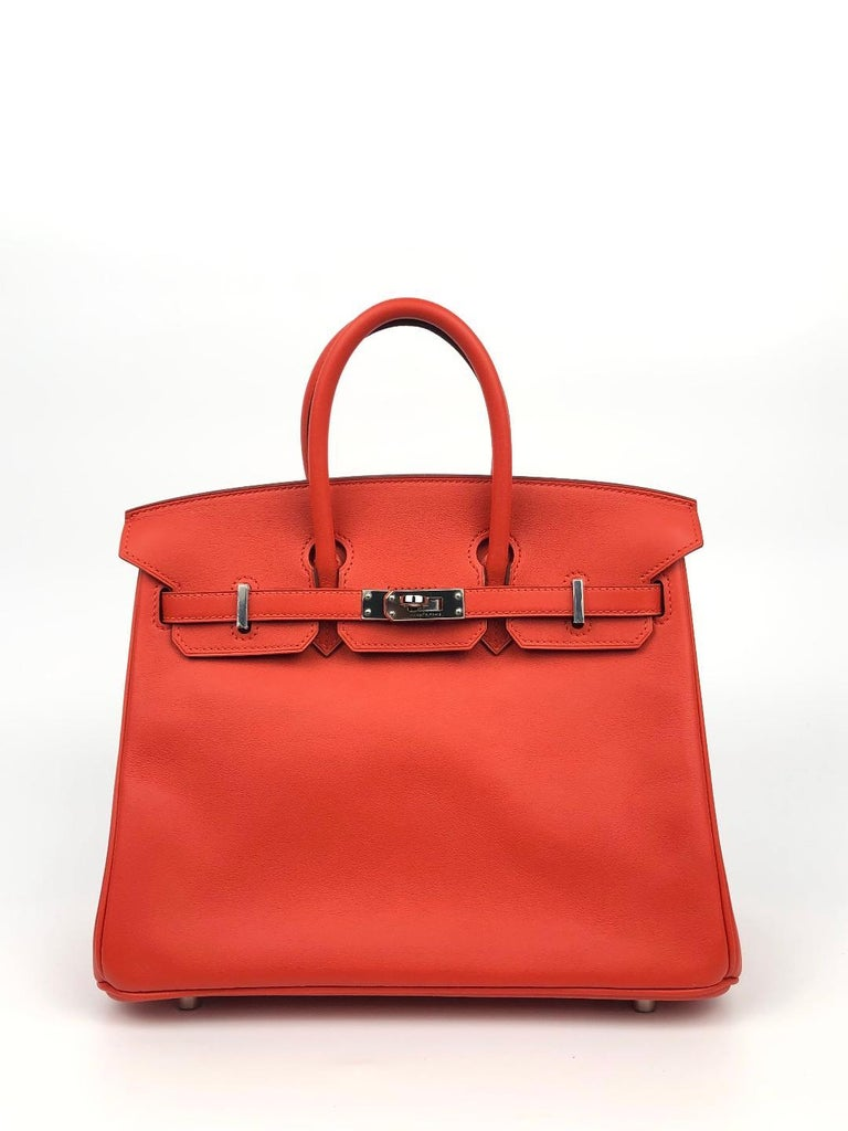 This authentic Hermès Rouge Tomate Swift Leather 25 cm Birkin Bag is in pristine unworn condition with plastic intact on the hardware.  Waitlists exceeding a year are commonplace for the intensely coveted classic leather Birkin bag.  Each piece is