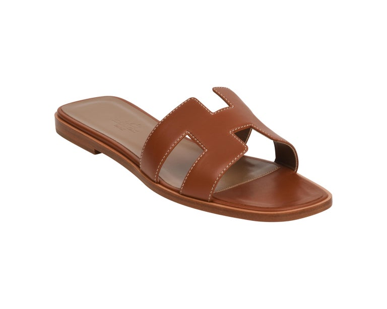 Guaranteed authentic Hermes Oran exquisite Gold box calfskin slide. The iconic top stitched H cutout over the top of the foot in sublime calfskin. Gold embossed calfskin insole.  Wood heel with leather sole.  Comes with sleepers, signature Hermes