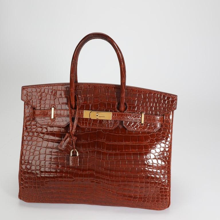 Listing Title: Hermès Shiny Miel Porosus Crocodile Birkin 35 GHW SKU: 108889  Handbag Condition: Very Good Condition Comments: Very Good Condition. Light scuffing to corners. Scratching to hardware. Indentations on interior. Please note: this item