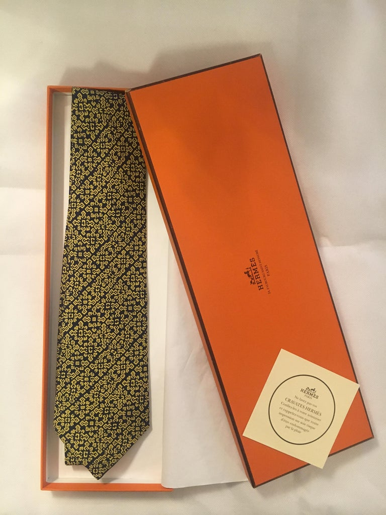 Beautiful HERMES tie in black / gold printed silk with geometric patterns, mint condition!  Beautiful HERMES tie Dominant colors: Black & Gold Reason: Geometric Material: 100% Silk Condition: new Packaging: Original box