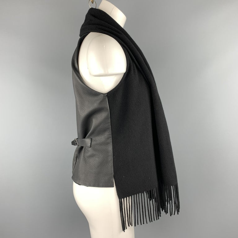HERMES vest features a cashmere frontal panel with a fringe trimmed scarf lapel collar, textured leather back with belt, and silk liner. Made in France.  Excellent Pre-Owned Condition. Marked: FR 40  Measurements:  Shoulder: 9 in. Bust: 38