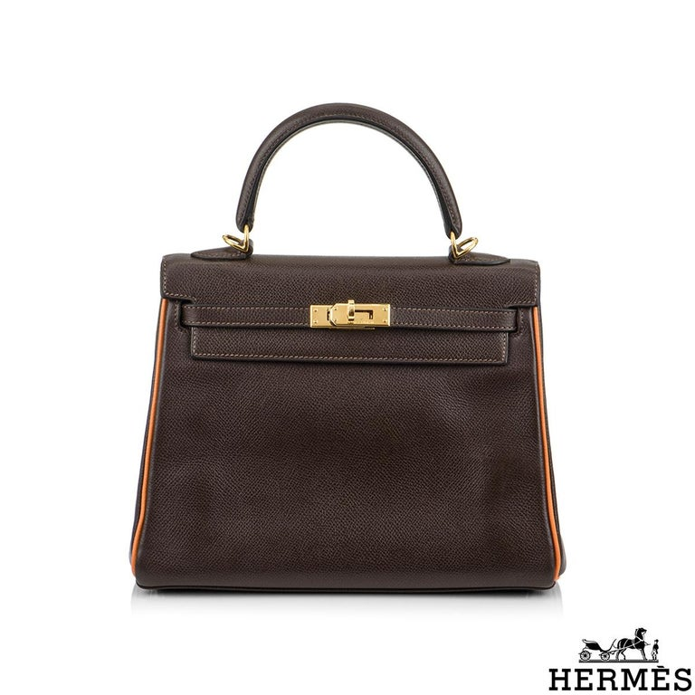 A beautiful vintage Hermès Kelly 25cm Bi colour Handbag. The chocolate brown colour is complimented with orange piping and gold hardware. The exterior of this Kelly features a retourne style in chocolate brown leather. It has a front toggle closure,