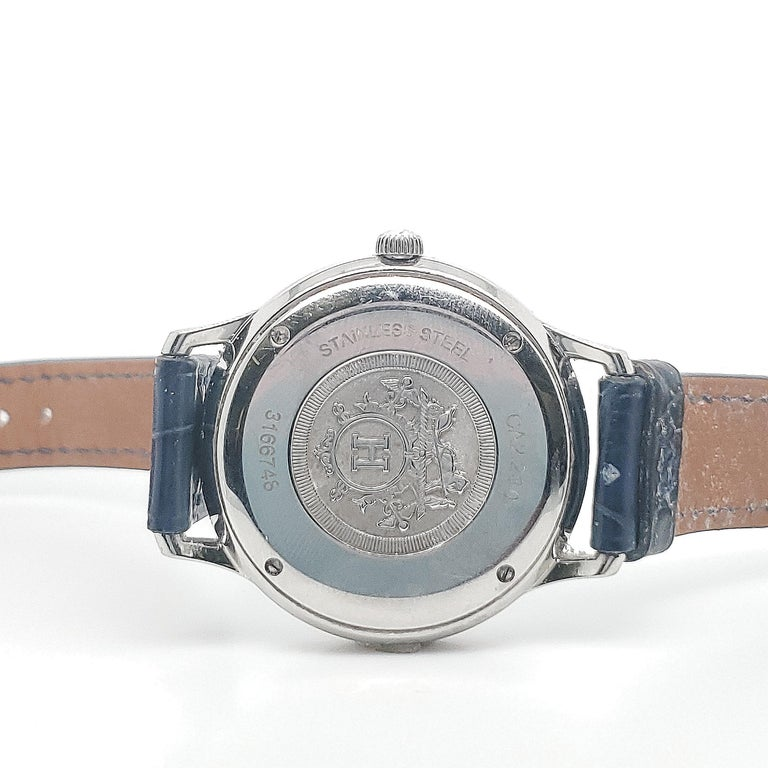 Authentic Hermes 'Slim d'Hermes' watch made in stainless steel. Watch bezel measures 32mm in diameter and is set with approx. 0.60 carats of round brilliant cut diamonds. Opaline silver plated dial, quartz movement. Alligator strap. Watches fits