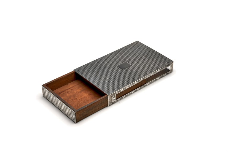 A fine and scarce sterling silver box by Hermes, in a rare example as a 'partner's box', in which the box can slide out in either direction as needed.  Marked on bottom.  Measures: 6