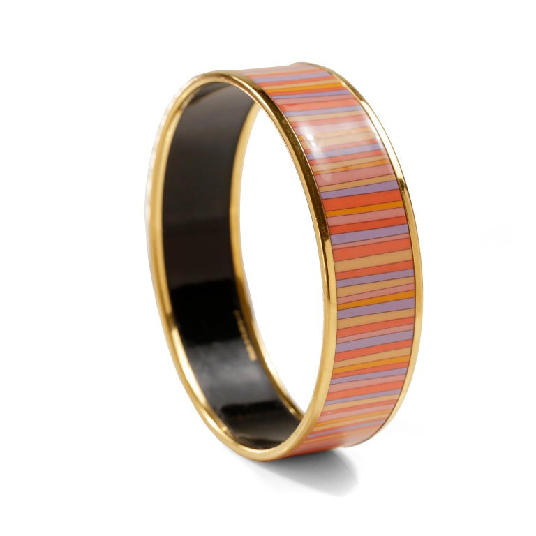 This authentic Hermès Striped Enamel Bracelet is in very good condition.  Gold tone edges, multicolored thin striped pattern in shades of orange, lavender, pink and yellow.  Made in Austria, F stamp.