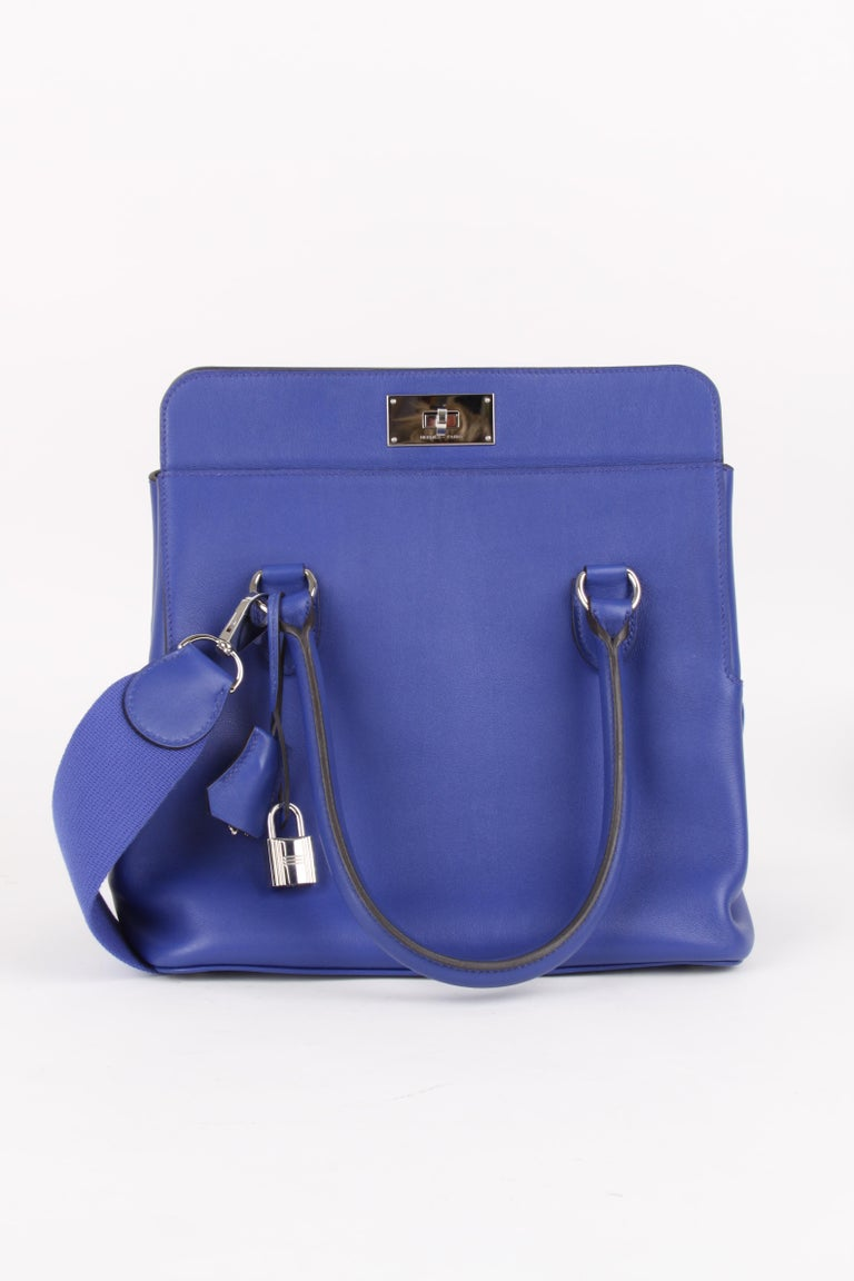 COLOR: Electric Blue   MATERIAL: Swift Leather  HARDWARE: Palladium plated hardware   COMES WITH: Raincoat, box, and dust cover, adjustable shoulder strap  ORGIN: France   CONDITION: 9/10  MEASURES: 26 x 25 x 18 cm Handle: 42 cm Strap: 80 cm
