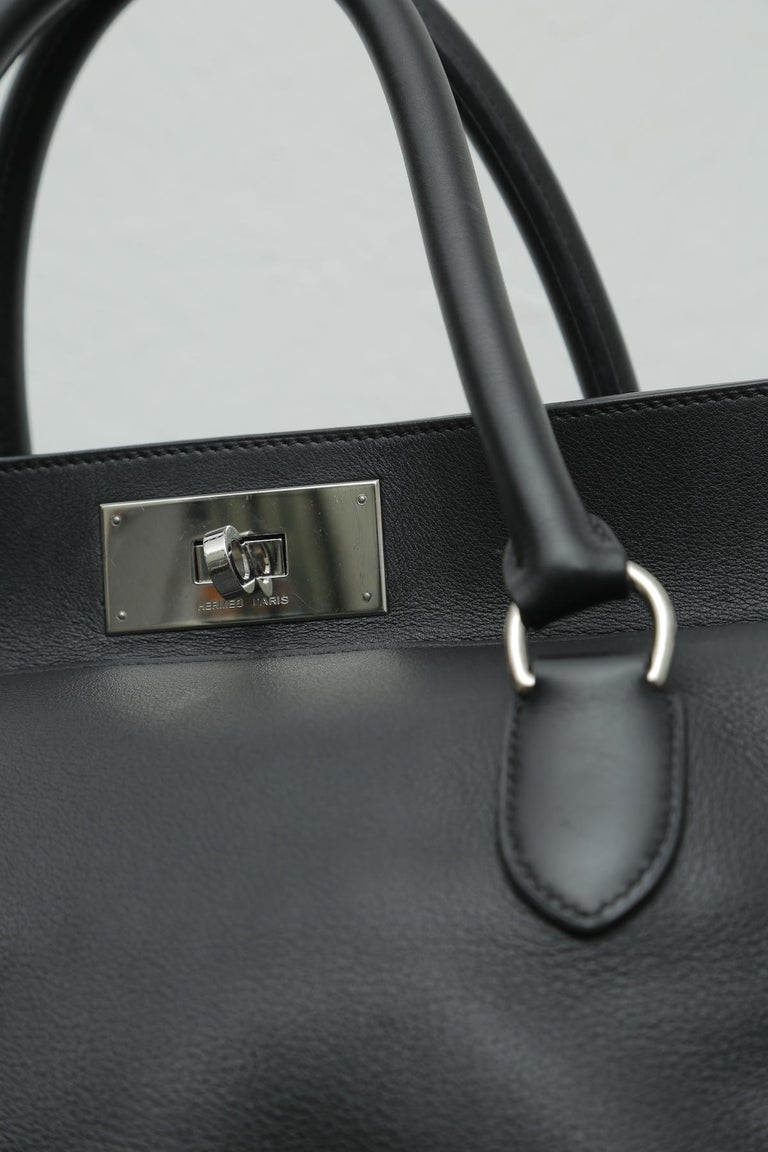 Hermes black toolbox 33 with silver hardware and detachable shoulder strap. This bag features dual rolled top handles, soft frame top and palladium tone hardware. Its turn lock closure opens to a beige fabric interior with patch pockets. This bag