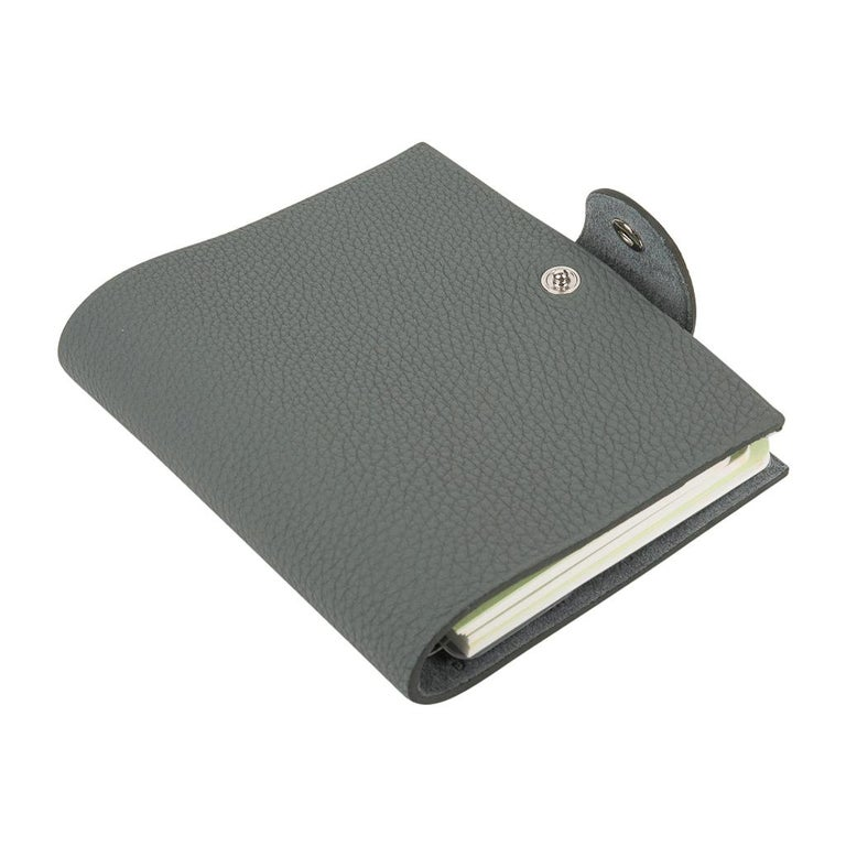 Guaranteed authentic Hermes Ulysse mini model notebook cover features Vert Amande in Togo leather. Palladium Clou de Selle snap.  Comes with a new Ulysse unlined notebook refill.    Each item comes with the signature Hermes box and ribbon. New or