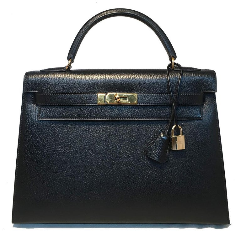 Hermes Black Noir Ardennes 32cm GHW Kelly Bag in excellent condition. Noir black ardennes leather trimmed with gold hardware. Signature twisting double strap flap closure opens to a black leather interior with 1 zip and 2 slit side pockets. No