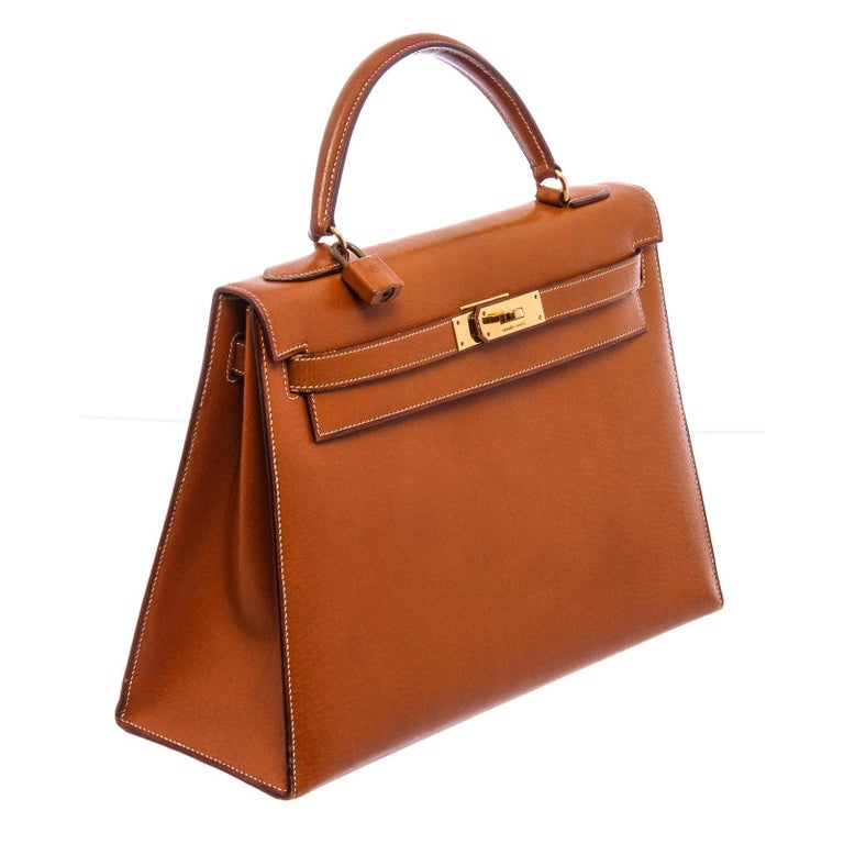 Brown Barenia leather Hermès Kelly Sellier 32 with gold-plated hardware, single flat top handle, protective feet at base, tonal leather lining, three interior pockets; one with zip closure and turn-lock closure at front. Include Lock, Keys and