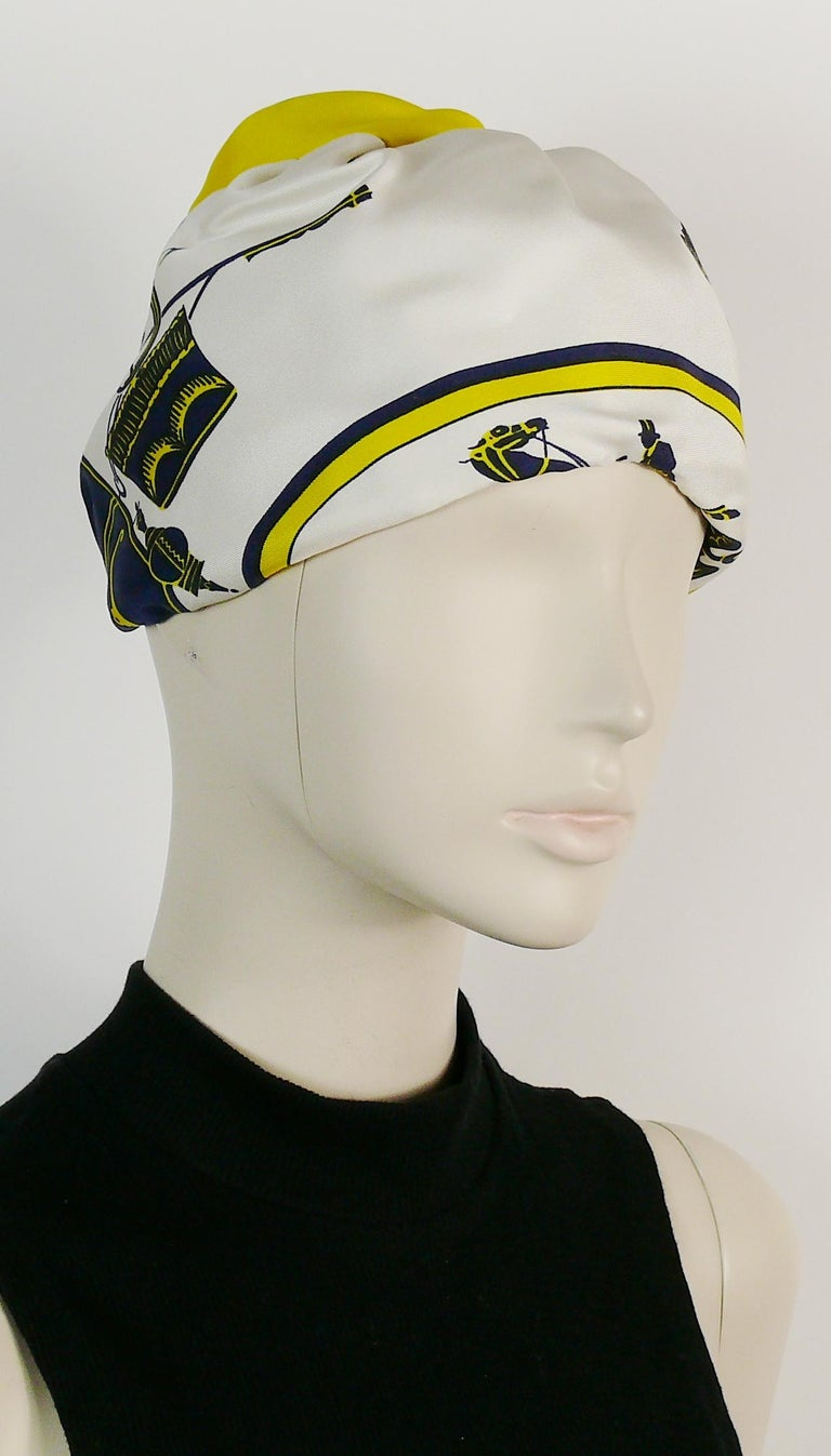 HERMES vintage silk turban hat printed with carriages in shades of blue and yellow on an off-white background.  Netted interior. Grosgrain headband. Elasticated neckline.  Label reads HERMES Paris.  Indicative measurements : circumference approx. 52