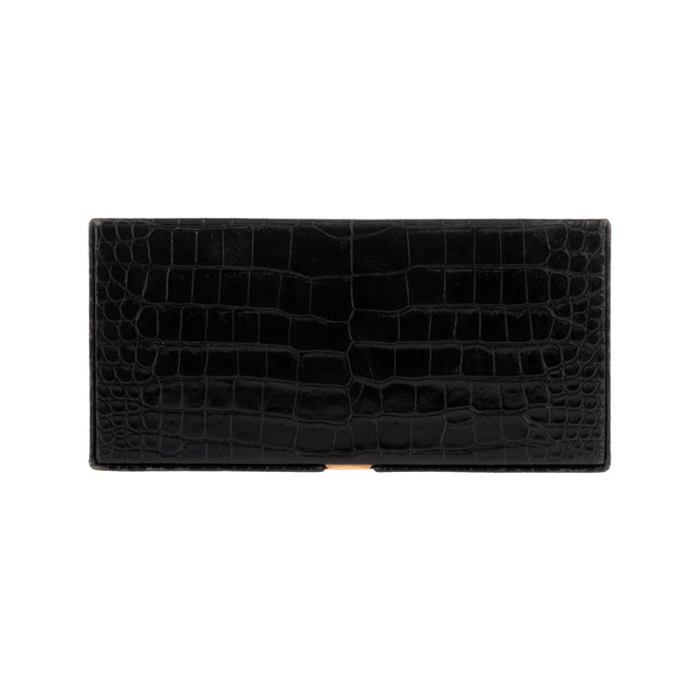 Hermès Vintage rectangular cigarette box in black crocodile. Gold plated metal coupling. Opening by press clasp on the hood. Interior: 2 cigarette compartments with black leather strap to hold cigarettes.