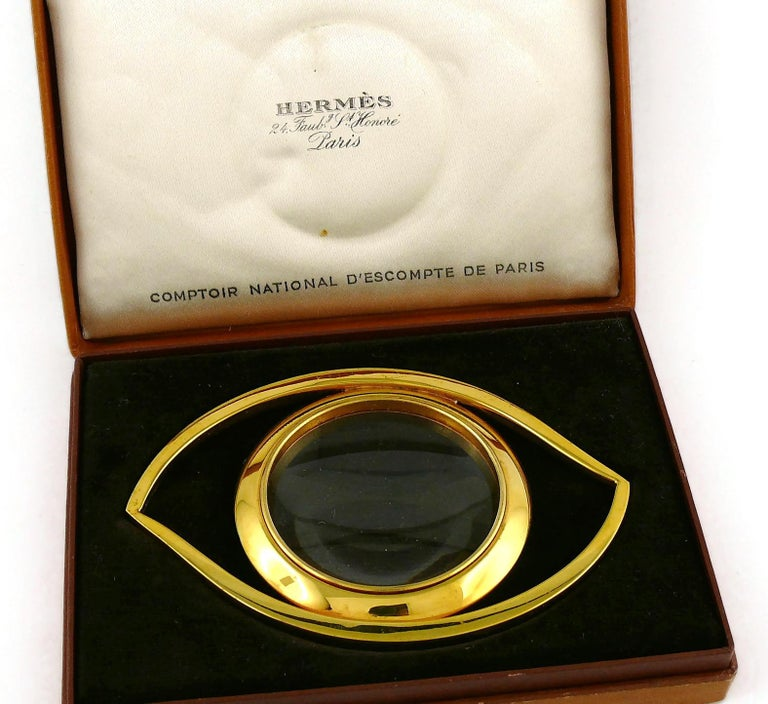 HERMES vintage gold plated desk magnifying glass and paperweight featuring a massive Cleopatra Eye.  Designed in the 1960's by JEAN COCTEAU for HERMES. This piece is directly inspired by the Egyptian Mythology and surrealist movement.  Embossed