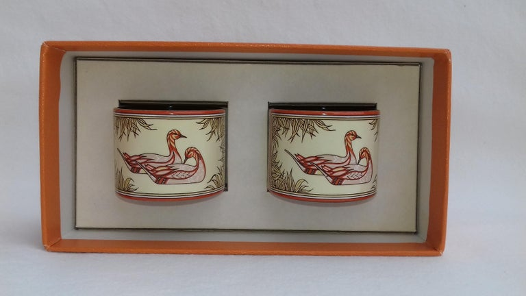 Beautiful Authentic Hermès Napkin Rings  Set of 2   Pattern: Ducks  Made in Austria  Not dated but probably from the end of the 20th century  Made of Printed Enamel  Colorways: designs in pinkish beige, beige, brick orange tones  Measurements: 4,2