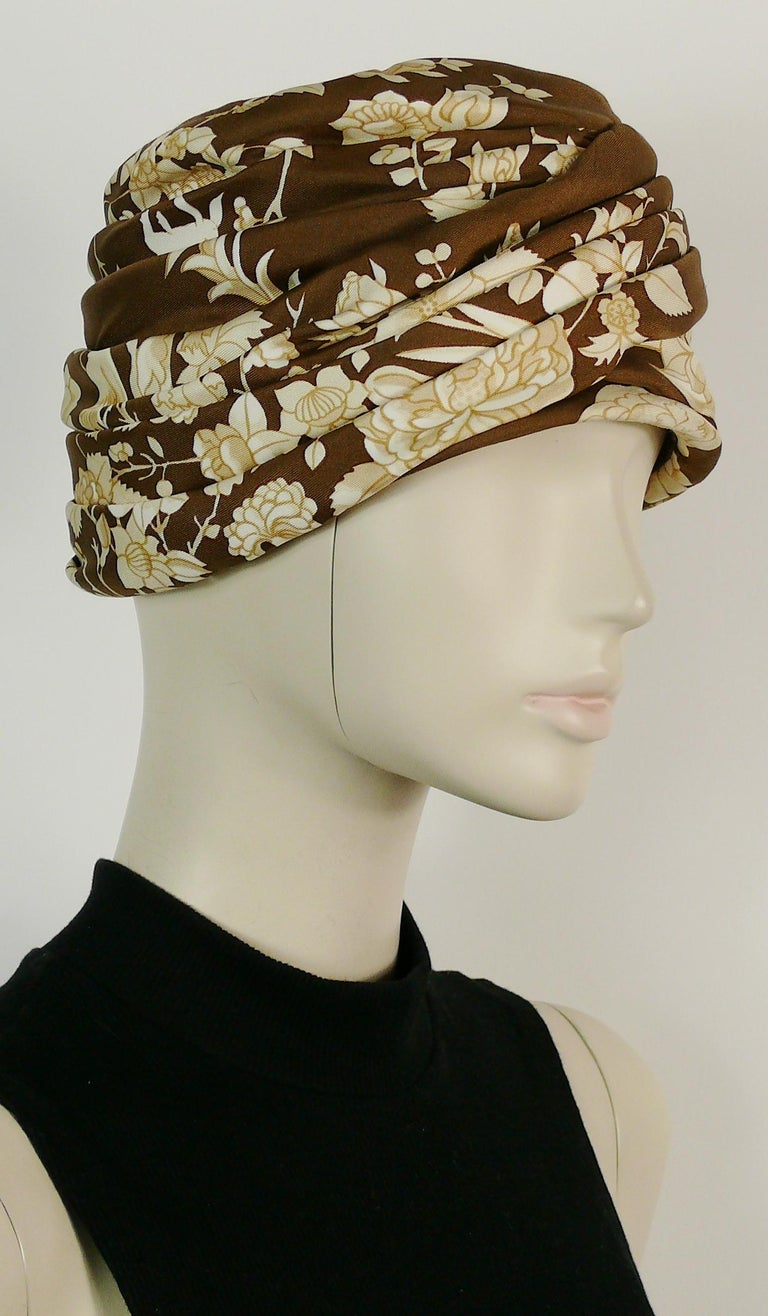 HERMES vintage silk turban hat printed with flowers and birds on a brown background.  Fabric lining. Grosgrain headband. Structured.  Label reads HERMES Paris.  Indicative measurements : circumference approx. 52 cm (20.47 inches) / height approx. 11