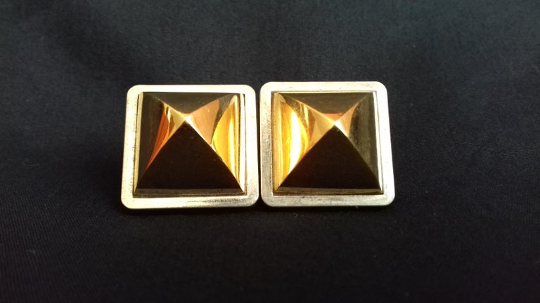 Beautiful Pair of Authentic Hermès Earrings  Pattern: Medor  Clip-on Earrings, no need to have pierced ears  Made of Metal  Colorways: Base is silver-tone, pyramids are golden