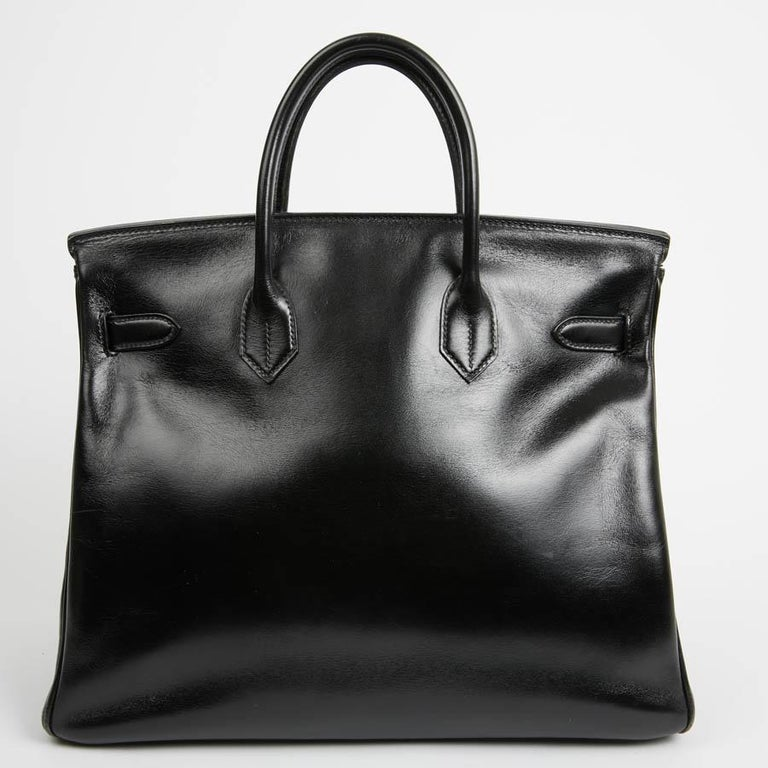 Sophisticated, Haut Courroies Bag said the HAC is in black Box leather, size 32. The jewelry is in gold metal. It has its zipper, bell, keys (2) and padlock. Opening by flap. The interior is in black leather with a large storage space and two flat