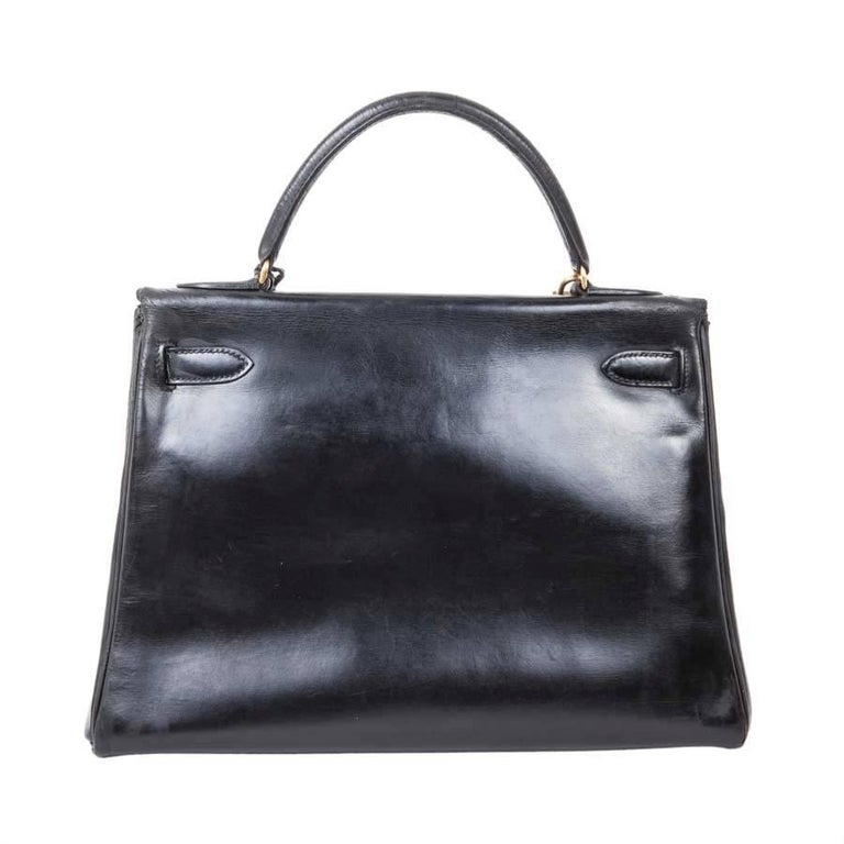 Hermès vintage Kelly 32 bag in black box leather. Stamp Z (year 1970).  It is in good used condition: the leather of the handle is gathered, the corners are very slightly patinated, little visible. The interior is leather with 3 pockets, one
