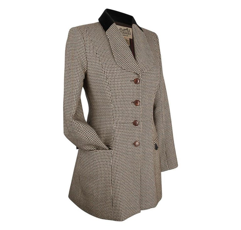Guaranteed authentic particularly beautiful 4 button single breasted Hermes vintage riding jacket. Shawl shaped lapel with a black velvet collar. Leather covered buttons. The fabric is an elegant small pattern of black and chocolate brown on a cream