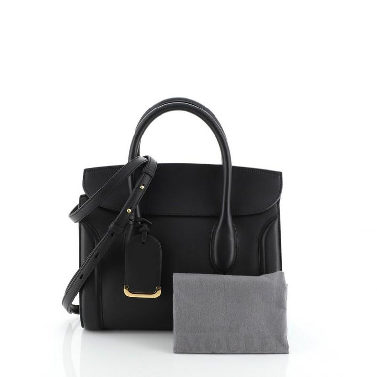 This Alexander McQueen Heroine Convertible Tote Leather 30, crafted from black leather, features dual rolled leather handles and gold-tone hardware. Its flap opens to a neutral microfiber interior with side zip and slip pockets.   Estimated Retail