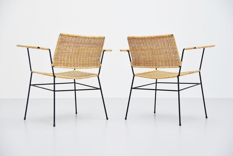 Fantastic pair of armchairs designed by Herta Maria Witzemann and manufactured by Erwin Behr, Germany 1954. The chairs have solid metal frames and hand woven cane seats and armrests. Super shaped pair of chairs and comfortable seating too. The