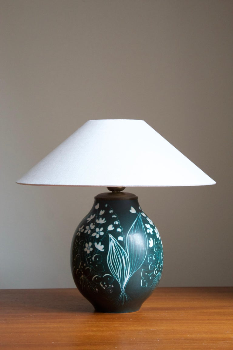 A table lamp produced by Rörstrand, Sweden, 1950. Designed by Hertha Bengtsson, (Swedish, 1914-1997). Signed.  Stated dimensions excluding lampshade. Height includes socket. Upon request illustrated lampshade can be included.  Other ceramicists