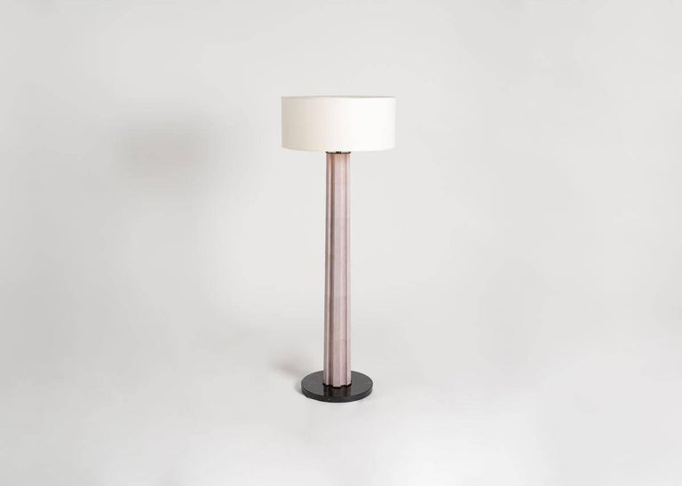 A columnar floor lamp clad in buckskin and resting atop a dark, circular base, Athéna possesses the elegant power of the monolith, and with its ambient glow, generates a quiet, ageless solemnity worthy of its classical namesake. 