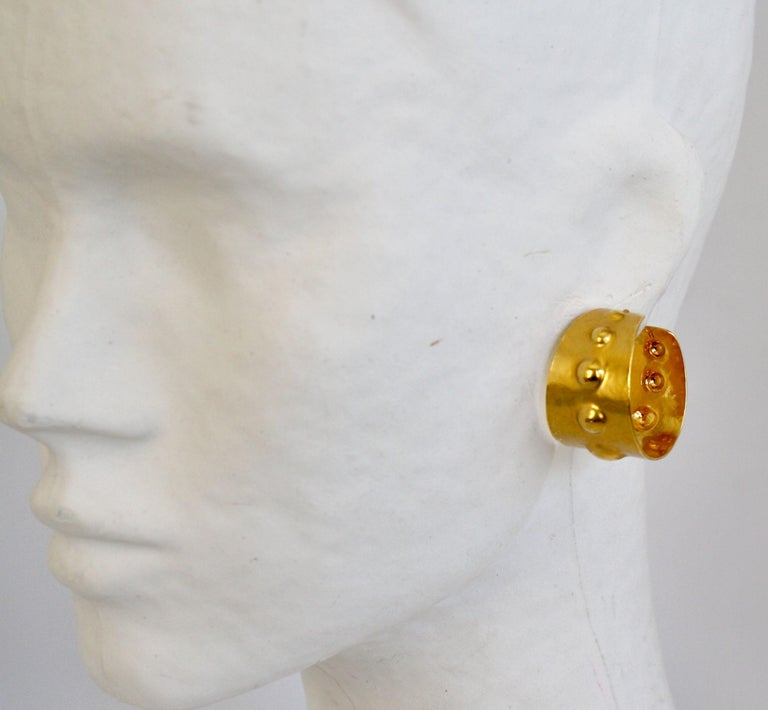 Hand hammered pierced gilded brass earrings from Herve van der Straeten. This designer is no longer producing jewelry, making all remaining pieces collectors items.